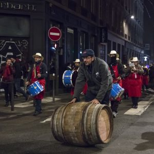 Viinitynnyrit vieritetään juhlasaattueessa Lyonin keskustaan juuri ennen puoltayötä.