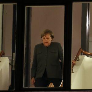Angela Merkel portaissa kuvattuna ikkunan läpi.