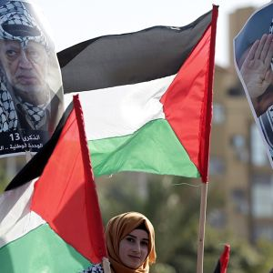 Palestiinalaiset viettivät entisen presidenttinsä Jasser Arafatin kuoleman 13. vuosipäivää 9.11.2017. Kuvassa nuori nainen, palestiinalaisten lippu sekä entisen presidentin Jasser Arafatin kuvia Gazassa.