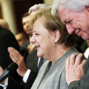 Angela Merkel hymyilee, ympärillä seisovat henkilöt taputtavat.