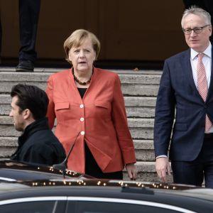 Merkel nousemassa autoon.