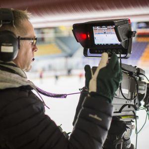 Mies käyttää videokameraa.