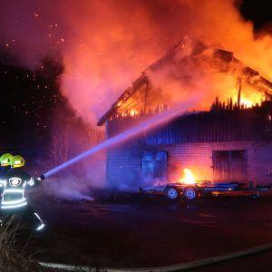 Palomiehet ruiskuttavat vettä liekkeihin.
