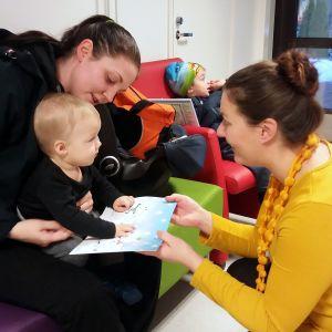 Kuvassa osastonhoitaja Anna-Leena Hohenthal antaa joulukalenterin äitinsä sylissä istuvalle pikkupojalle.