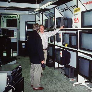Myyjä esittelee asiakkaalle televisioita myymälässä vuonna 1991.