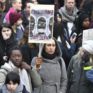 Tukholman keskustassa osoitettiin mieltä orjakauppaa vastaan 25.11.2017. Uutiskanava CNN oli samalla viikolla esittänyt kuvamateriaalia Libyan siirtolaisleiriltä. Kuvassa mielenosoittajien kylttejä, joissa orjuuden vastaisia iskulauseita.