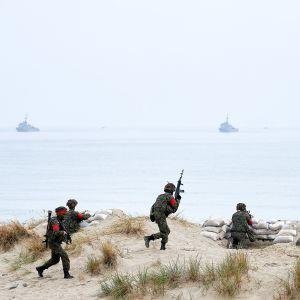 sotilaat juoksevat rannalla