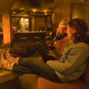 Ystävät nauttivat ravintolassa viinilasilliasia takkatulen ääressä.