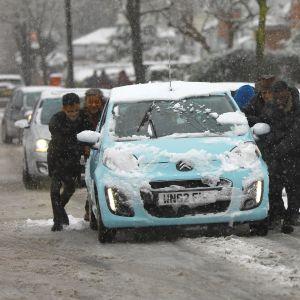 Lumisella kadulla neljä miestä työntää autoa, kadunvarteen on pysäköity lisää lumisia autoja.