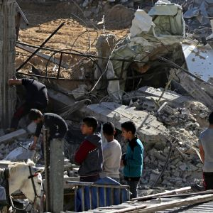 Pojat katselevat tuhotun Hamas-sotilaskohteen raunioita Gazan pohjoisosassa.