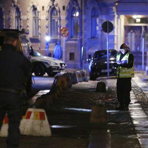 Kuva öiseltä kadulta. Seinästä roikkuu poliisin eristysnauhaa. Kuvan keskellä seisoo poliisimies keltaisissa huomioliiveissä.