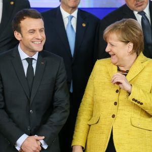 Macron ja Merkel EU-johtajien yhteiskuvassa. Macronilla on tumma puku, Merkelillä keltainen jakkuasu. Molemmat hymyilevät.