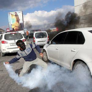 Kuvassa palestiinalaismies on heittämässä kyynelkaaskranaattia.