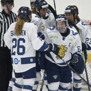 Suomen naisten jääkiekkomaajoukkue juhlii maalia.