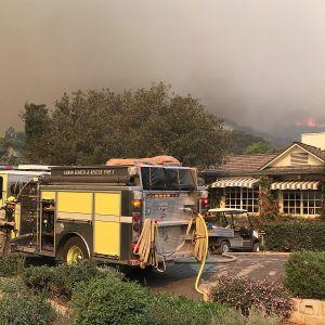 Keltainen paloauto talon edessä, taivas on harmaa savusta ja taustalla olevilla vuorilla näkyy liekkejä.