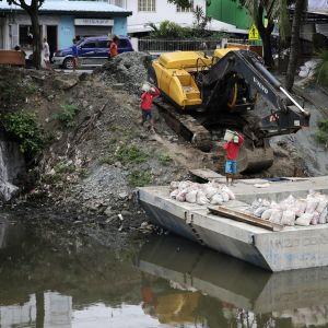 Kuvassa kaivinkone ja kolme miestä tekemässä tulvavallia.