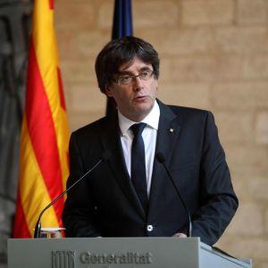 Mustapukuinen mies puhuu Katalonian punakeltainen lippu taustalla