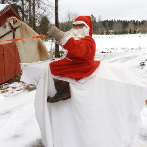 Joulupukki ratsastaa hevoshahmolla, jota ratsastaja kannattelee itse