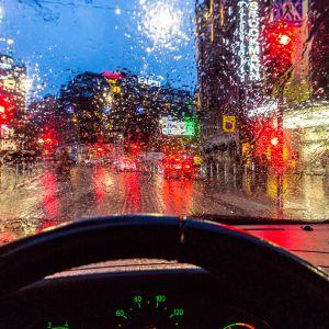 Sateinen Helsinki nähtynä auton tuulilasin läpi illalla.