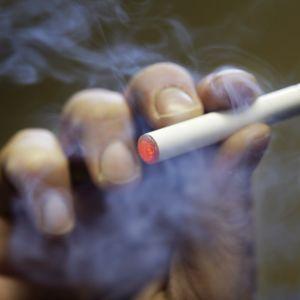 En hand håller i en elektonisk cigarett.