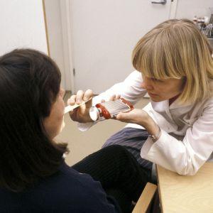 Läkare lyser in i munnen på en patient