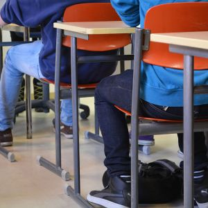 Elever sitter vid sina bord i klassrummet.