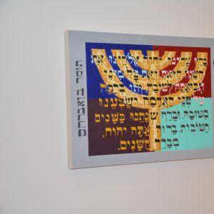 En tavla av en sjuarmad ljusstake. Texten är en bön för förmögenhet på hebreiska.