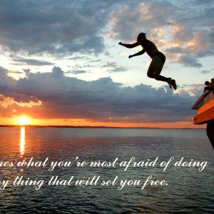 En människa hoppar i vattnet från en båt i solnedgången.