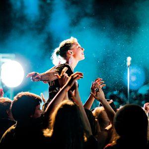 Tjej som sitter på någons axlar under en konsert