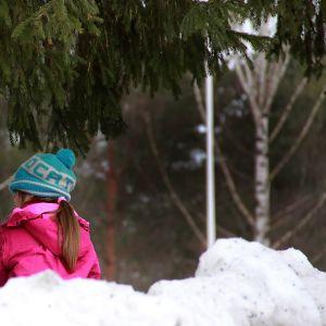 Två barn sitter i en snödrivar och pratar.