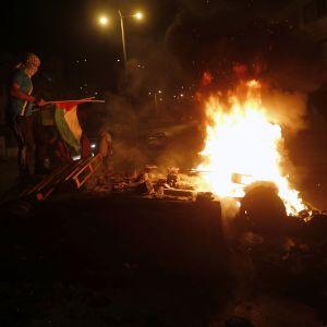 Palestinier tänder eld på en israelisk bil i Nablus efter sammandrabbningen vid Josefs grav på Västbanken.