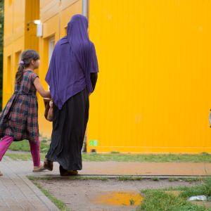 En mamma och sin dotter i ett bostadsområde.