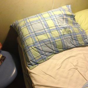 dyna och skrynkliga lakan i en obäddad säng