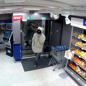 En man stiger in i en Siwa-butik med ansiktet dolt.