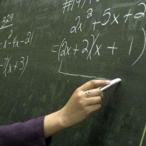 En lärare skriver matematiska formler på en tavla
