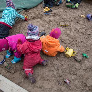 Barn leker i sandlåda