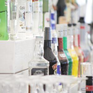 Alkoholflaskor bakom disken på en bar.