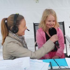 Flicka blir intervjuad av Yles repportrar.