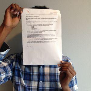 En somalisk man håller upp Migrationsverkets brev framför sitt ansikte.