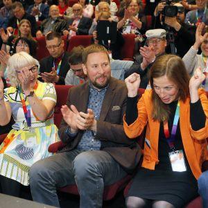 Li Andersson i orange jacka jublar med händerna i knytnävar. Paavi Arhinmäki sitter bredvid henne och applåderar tillsammans med andra partimedlemmar i bakgrunden.