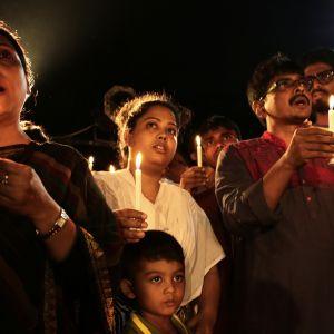 Människor hedrar offren i terrorattacken mot en restaurang i Dhaka.