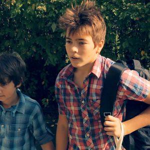 Två pojkar står. En håller i en vas med två rosor.