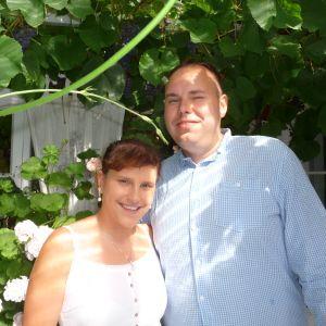 profilbild på valenta herold-sarkanen och roger sarkanen i deras trädgård. Bakom dem stora pelargonior och vinranka