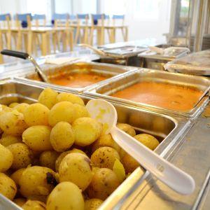 Potatis och köttbullar väntar på hungriga elever i skolmatsal.