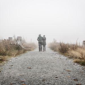 Två personer håller om varandra och går längs en grå väg. Bilden är tagen bakifrån.