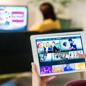 En kvinna tittar på traditionell tv i bakgrunden, och en annan tittar på tv via datorplatta i förgrunden.