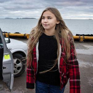 Linnea Skog på väg bort från en bil i vilken en annan flicka sitter
