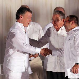 """Colombias president Juan Manuel Santos och Farcledaren Rodrigo Londono Echeverri, alias """"Timochenko"""" gratulerar varandra vid underteckningsceremonin. Kubas president Raul Castro följer med i bakgrunden"""