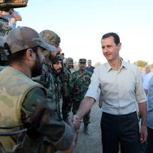 Bashar al-Assad skakar hand med en soldat.