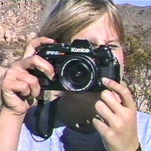 Eva Vitija fotograferad i unga år med en kamera framför ansiktet.